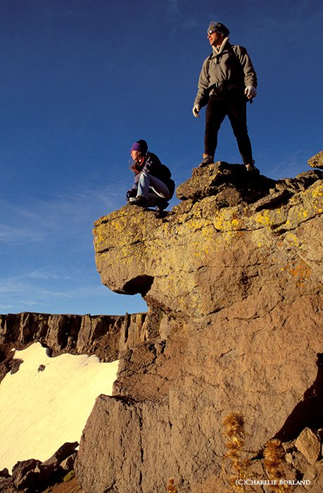 two climbers standing at an ourcropping on a cliff, looking over a valley and an expanse of blue sky