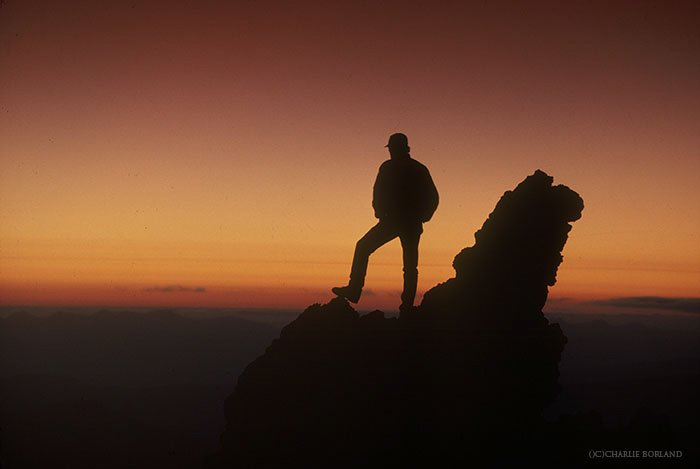silhouette of a hiker at the top of a rockface, looking over at the sunset on the horizon - adventure photography tips