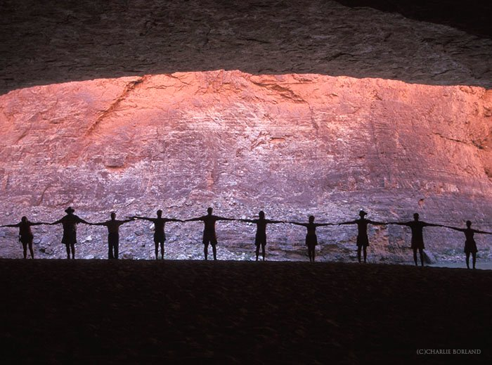 silhouette of a chain of people holding hands in front of a rock face lit purple and orange by the sun