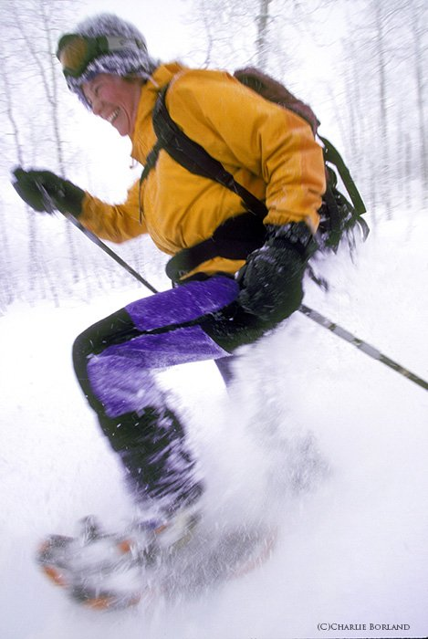 skier in a yellow jacket and blue pants, skiing down a snowy slope