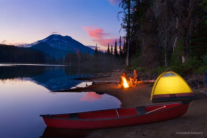 campers with a bonfire, a yellow tent, red boat by a lake shore, mountain on the horizon in a purple orange sunset