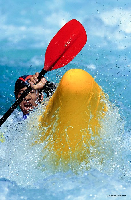 close up of person rowing the rapids in a yellow boat with red oar in bright crystal blue waters