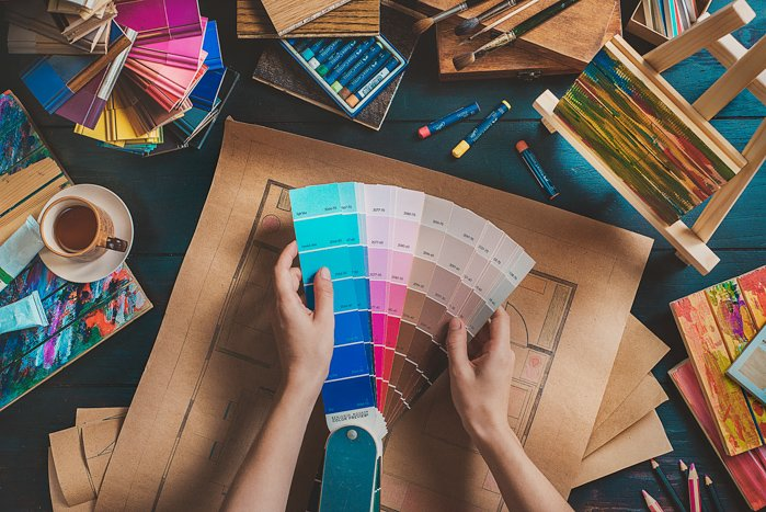 Overhead shot of a person looking through color pantones - colors that contrast with blue