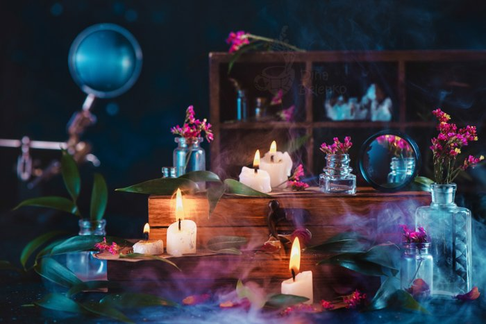 Wizard or witch workplace with burning candles, herbs, vintage wooden boxes and smoke. Dark fantasy still life with blue and orange color scheme