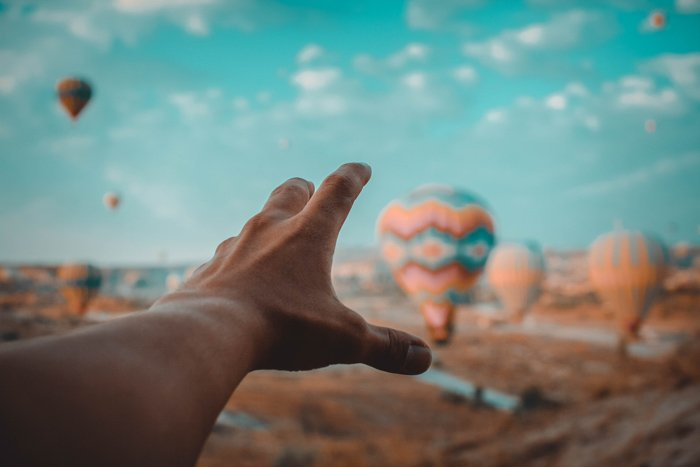 A forced perspective photo of a persons hand reaching toward hot air balloons using orange and teal color scheme