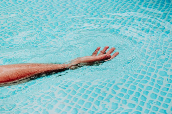 A persons hand spread out in water using orange and blue color scheme