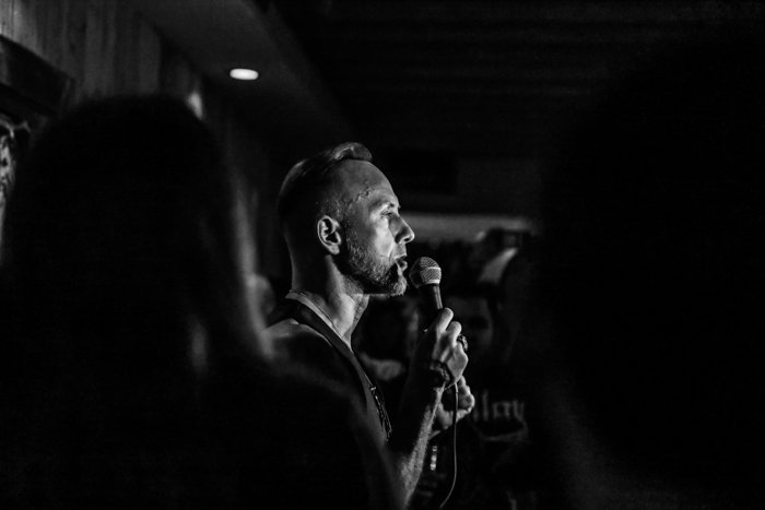 A black and white event photography shot of a man speaking or singing into a microphone onstage