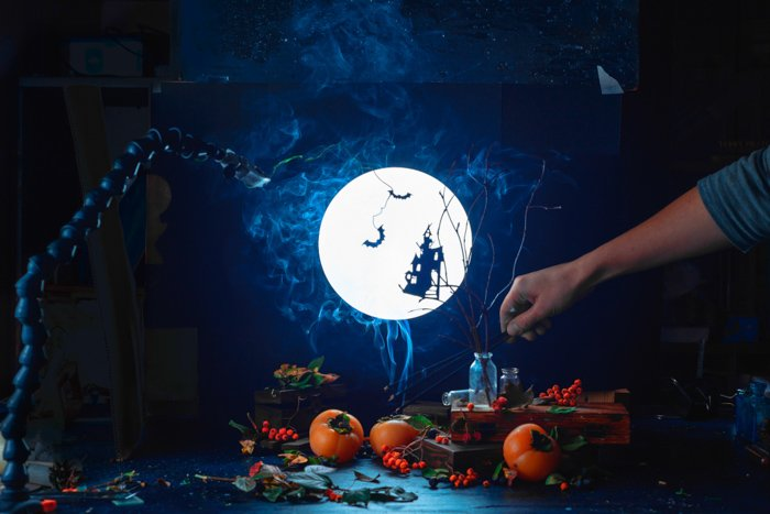 A still life featuring spooky halloween silhouettes, a full moon and other photography props