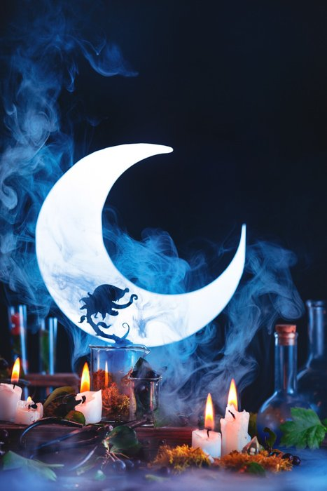 Atmospheric Halloween still life featuring the silhouettes, a crescent moon and other spooky props