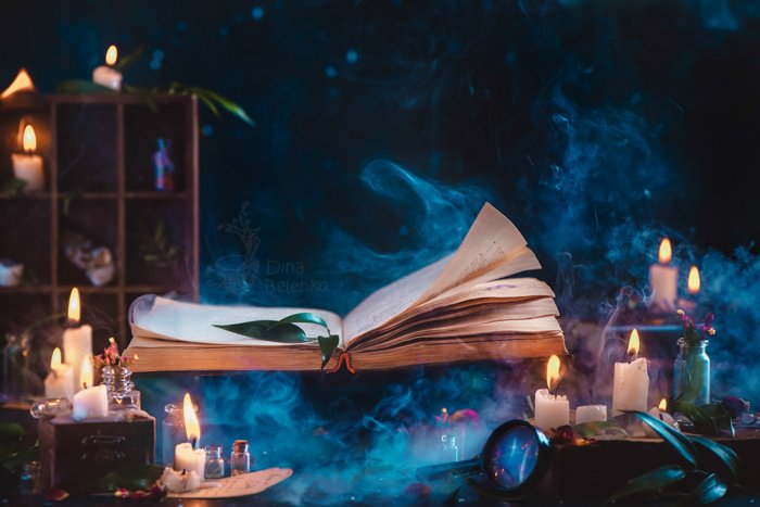 A spooky Halloween photography still life featuring a spellbook, candles and other photography props