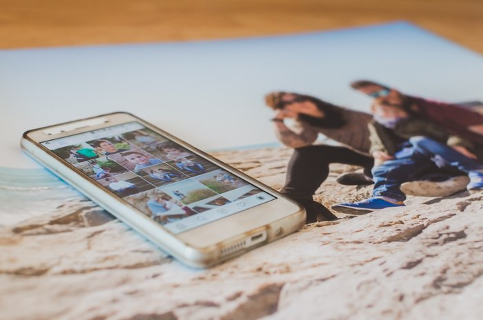 A smartphone opened on gallery, laying on a printed photo resized in Lightroom