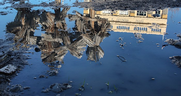A stunning photo of artwork and architecture reflected in a puddle, perfected by using Photoshop patch tool