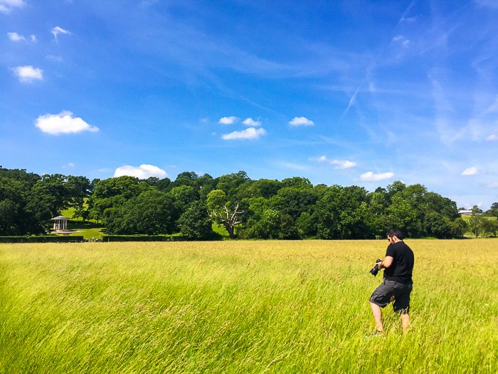 man with a camera walking through a field of bright green grass beneath a deep blue sky