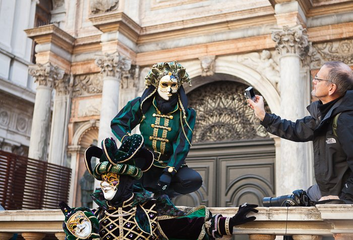 Man taking a photo of two actors is masks and costumes, performing in front of an old, historical structure