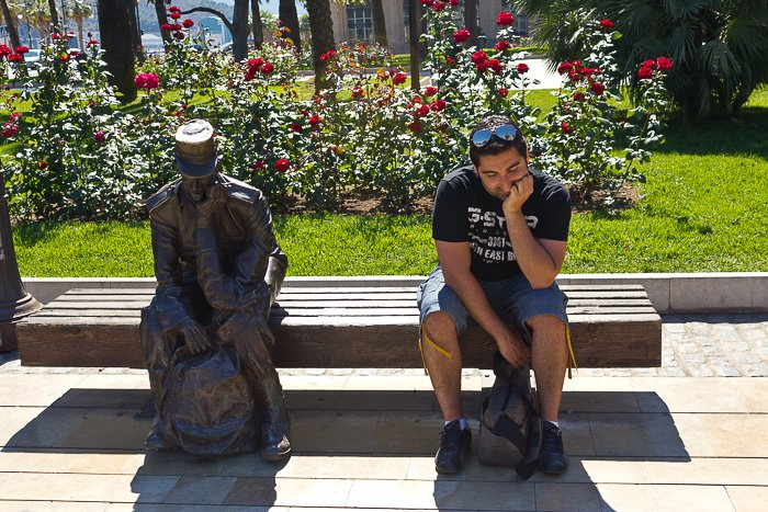 outdoors, in front of a patch of red flowers, a man sits next to a statue, imitating it's thinking posture