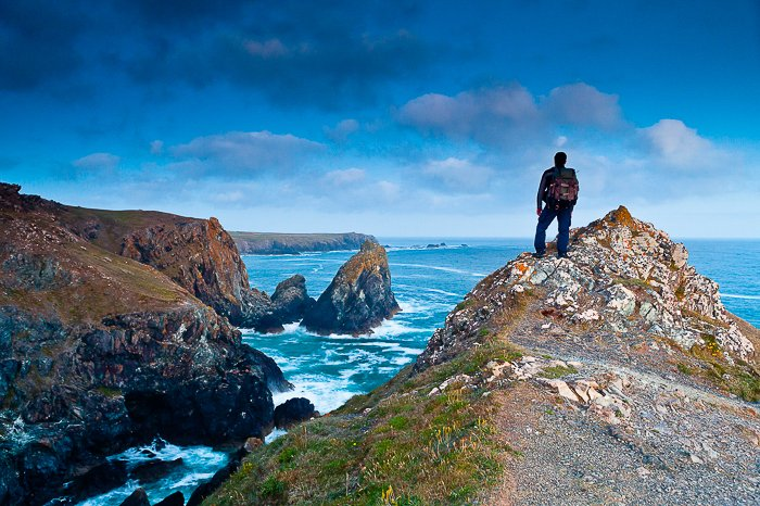 View from behind of a man standing at the top of an outcropping of rock overlooking a rocky shore and bright blue sea and sky