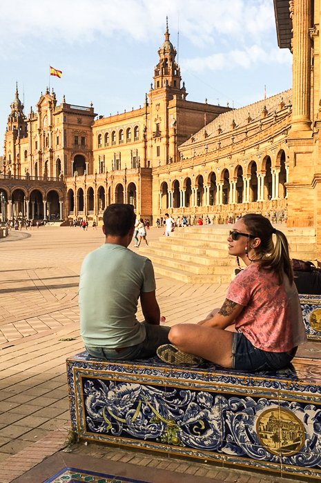 a travelling couple sitting on the decorated steps in the shade of a building, looking across the square at historic architecture