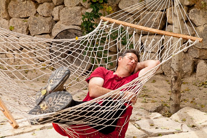 man in a red shirt asleep in a hammock hanging outdoors, a rocky wall behind him