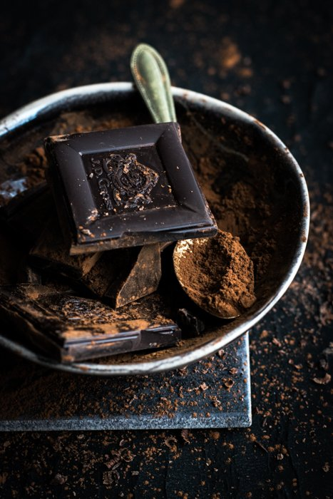 A close up of a bowl of pieces of dark chocolate and a spoon covered with powdered chocolate