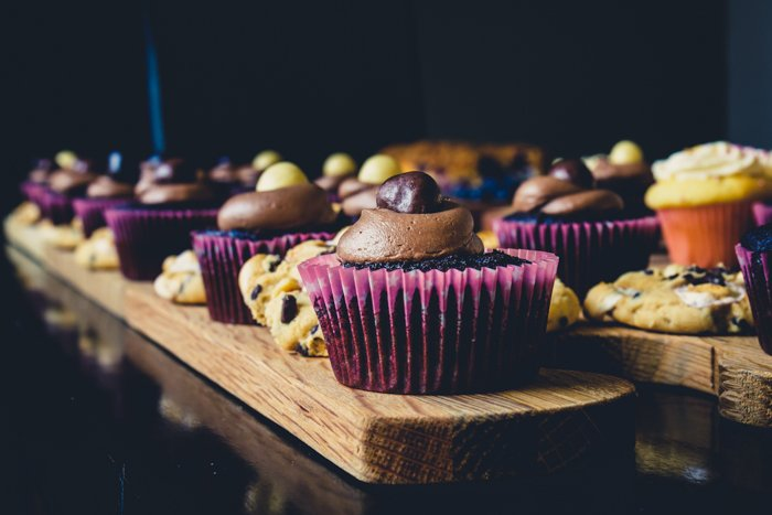 A close up of cupcakes in a row on a table, with dark purple cupcake paper