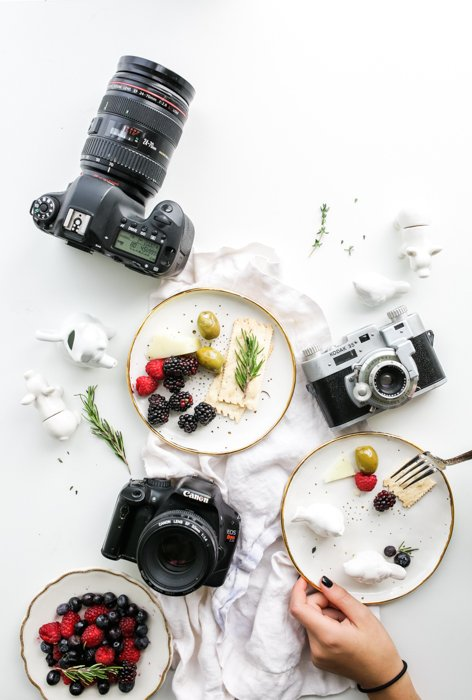 preparing flatlay of plates of fruit desserts and different cameras for food photography on a white table