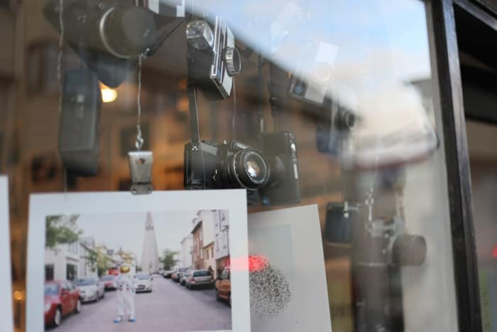 A display of cameras and photos in the window of a photography shop