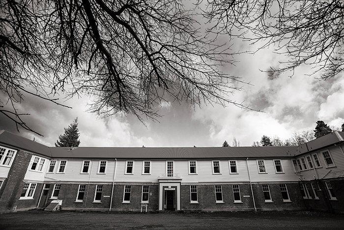 black and white photo of the front of the Queen Mary Hospital Nurse's Hostel, bare branches on a nearby tree, hues adjusted to bring out more detail in the photo