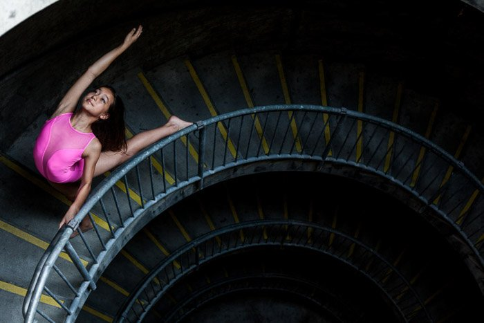 A young girl in pink ballet dress dancing on a dark stairwell - best settings for portraits