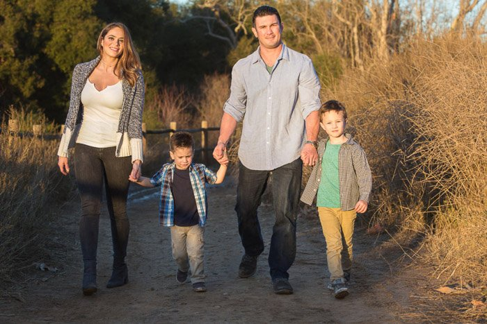 A portrait of a family of 4 smiling and holding hands while walking in the countryside