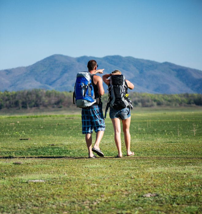 A Young couple walking together in an empty field using central composition