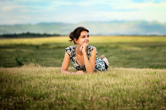Attractive young woman outdoors in a wide open field at Doi Tao, Thailand.