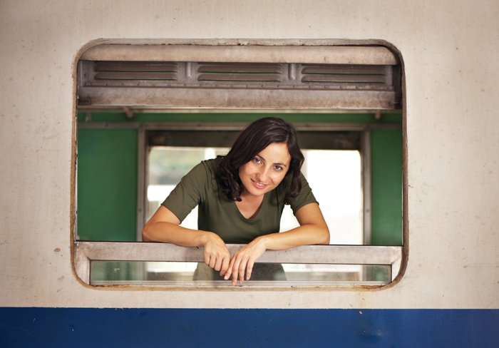 Attractive young woman looking out the window of an old train, demonstrating central composition framing.