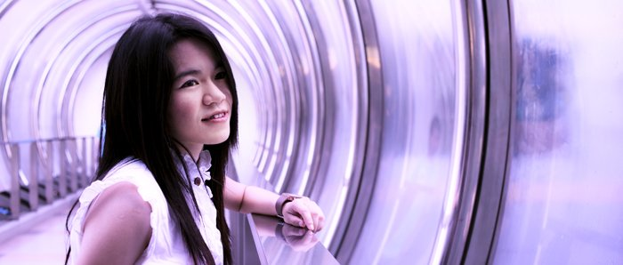 A cinematic photography portrait of a female model standing in a purple tunnel