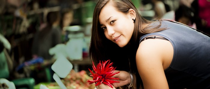 A cheerful cinematic looking portrait of a female model posing with red chillis in a market