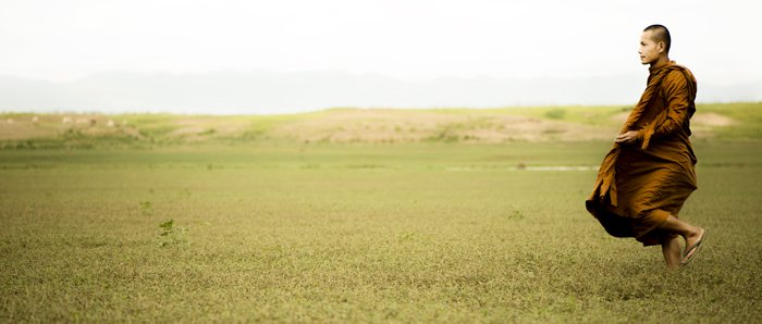 bright and airy cinematic photography portrait of a monk in a green field