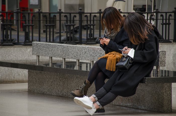 Street photo of two girls sitting on a bench and using smartphones, demonstrating mid and dark tones in images