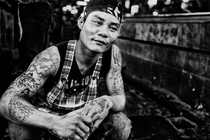 A black and white portrait of a Thai butcher kneeling on the ground - photography contrast