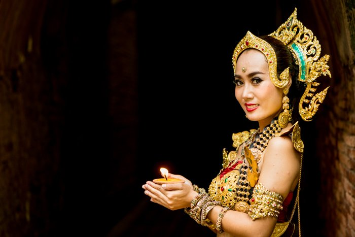 A beautifully costumed smiling thai dancer poses aginst a dark figure to ground background