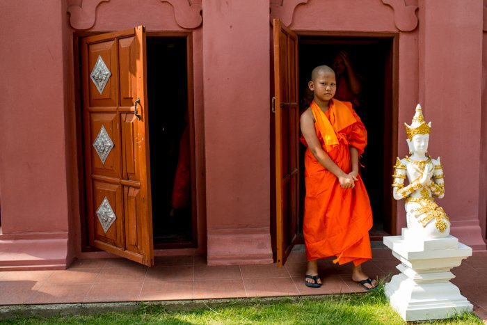 A young novice monk in orange robes standing outside a doorway - figure photography composition
