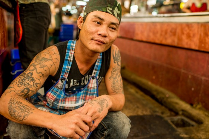 A street portrait of a Thai butcher kneeling on the ground - photography composition