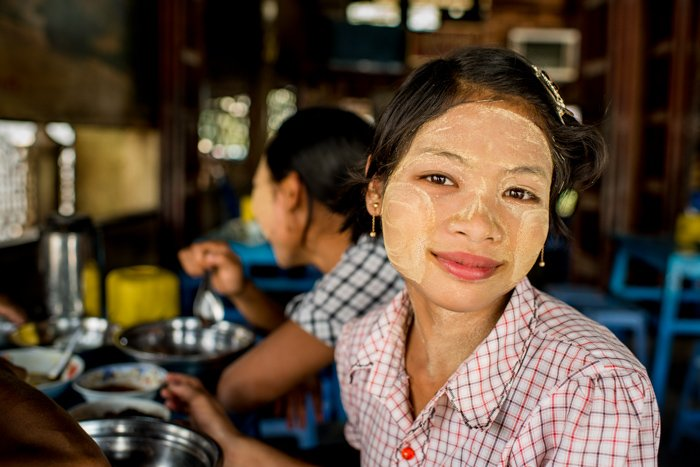 A smiling Karen woman with face-paint - figure to ground photo composition