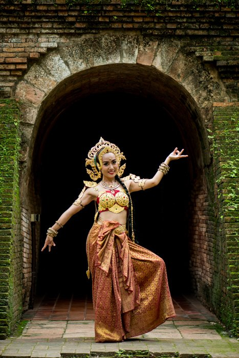 A beautifully costumed smiling thai dancer poses in front of a tunnel - photography composition tips