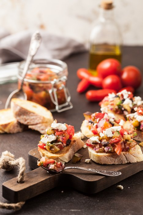 Canapés on a wooden tray, tomatoes, french bread slices, cheese, and a bottle of olive oil on the table.
