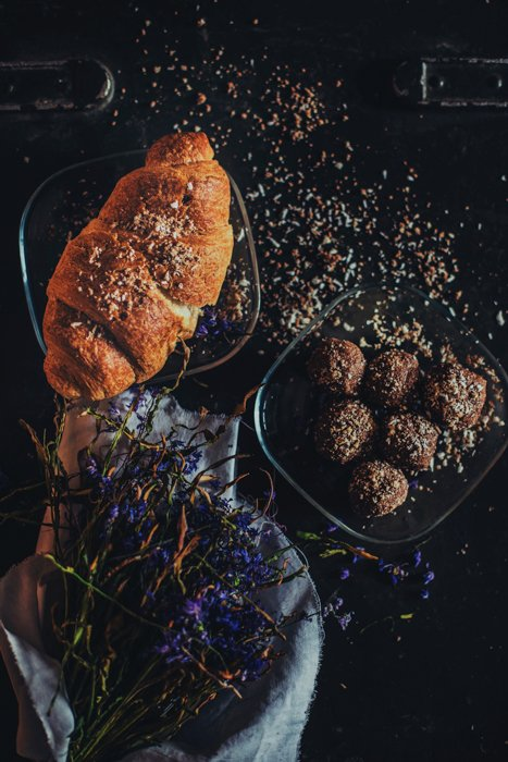 baguette and a plate of meatball on a dark table with dried blue flowers, crumbs scattered over everything