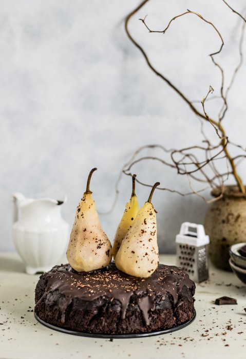 three pears on top of a chocolate cake, a dried plant in the background