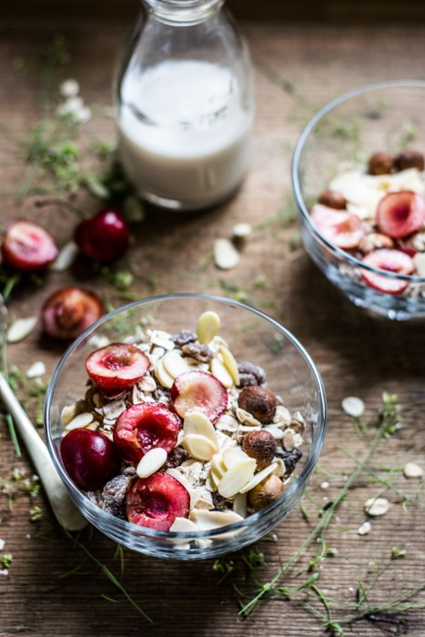 fruit and oats in a bowl, near a bottle of milk on a wood table