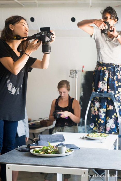 women holding DSLR cameras standing on chairs, photographing food on a table