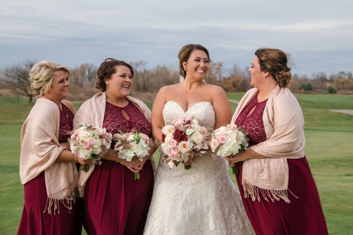 A bride posing with her bridesmaids in deep red gowns, holding bouquets, outdoors on a sunny day