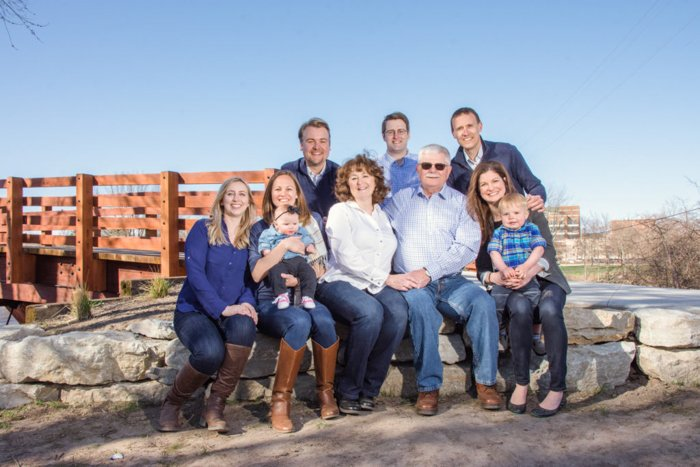 A family group photo outdoors on a bright day, family wearing jeans and boots, a wood bridge and blue sky behind them