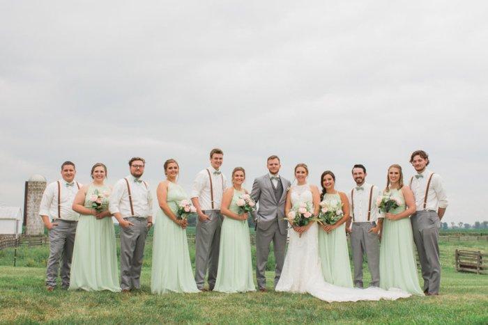 A wedding entourage posing in a grassy field, bridesmaids in mint gowns, groomsmen wearing suspenders